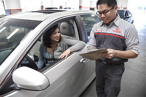 Toyota Service Tech talking to Women in a vehicle